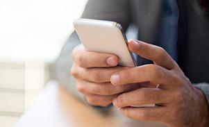 Gepflegte Männerhände, die ein weißes Smartphone halten.