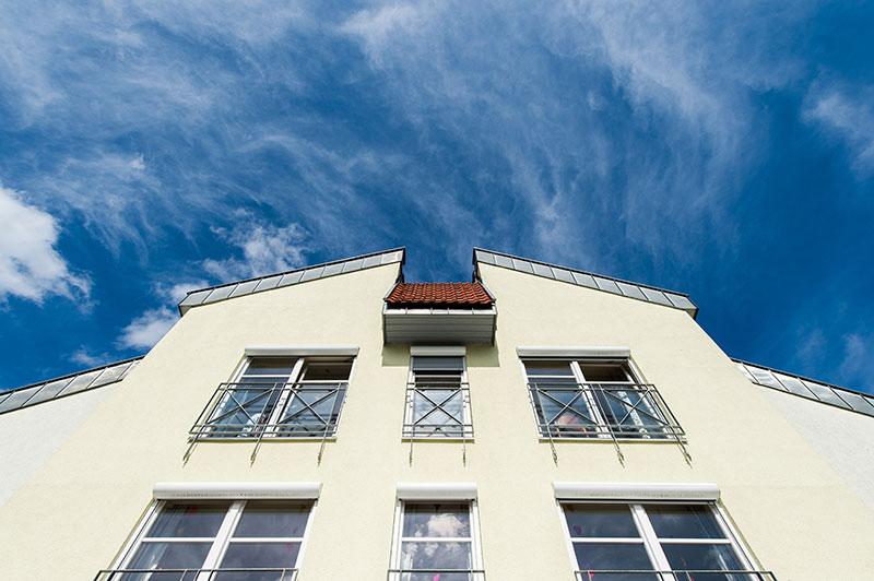 Blick von unten auf die helle Fassade eines Seniorenheims, vor blauem Himmel.