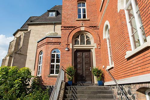 Eingang eines Seniorenheims mit roten Klinkern, brauner Holztür und Steintreppe.