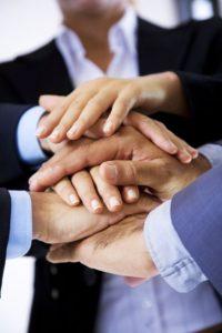Übereinanderliegende Hände von Männern und Frauen in Business-Kleidung.