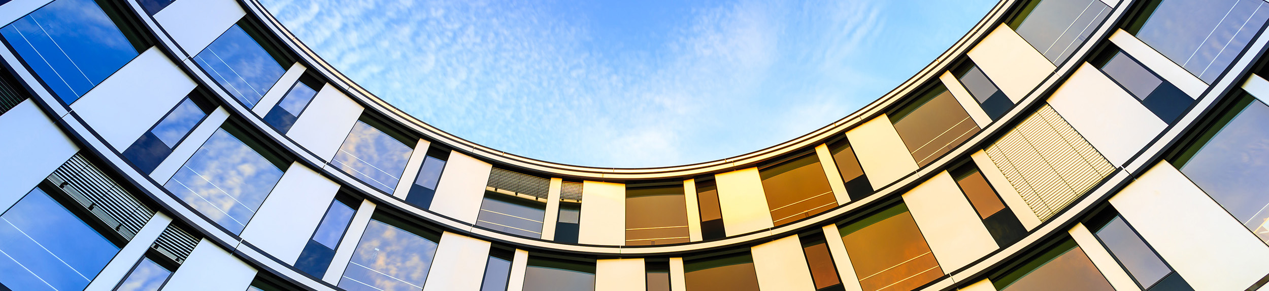 Blick von unten auf die halbrunde Fassade eines modernen Seniorenheims bei Sonnenuntergang.