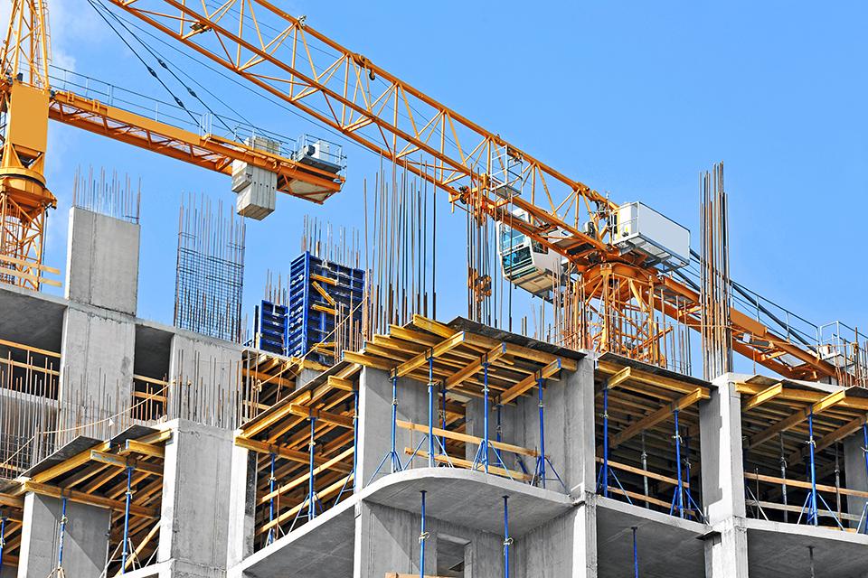 TERRANUS Wissenswert - Baustelle aus Froschperspektive mit gelbem Kran vor blauem Himmel